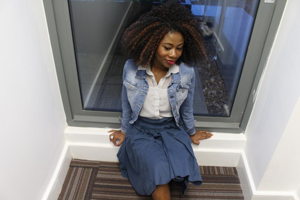 Blue paper bag skirt, washed blue jean jacket, grey blue blouse, white heels,crochet braids, girl sitting on the floor, thinking, OOTD