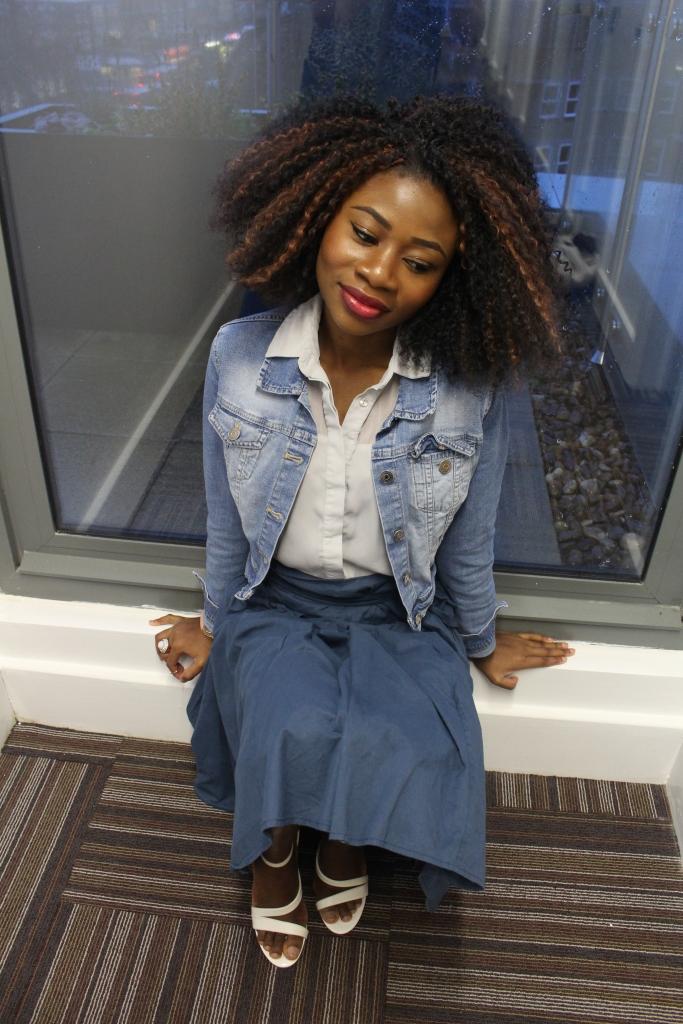 Blue paper bag skirt, washed blue jean jacket, grey blue blouse, white heels,crochet braids, happy moods, sitting on the floor happy